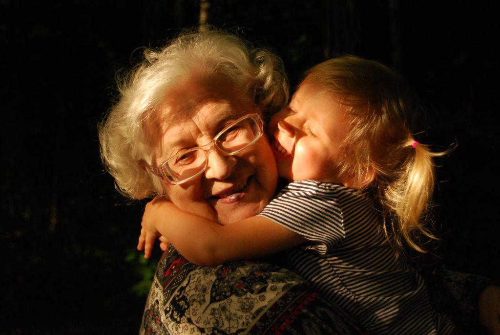 Väikelaps kallistamas vanaema